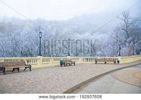 View Of Rime-covered Park With Benches, Lights On Winter Day