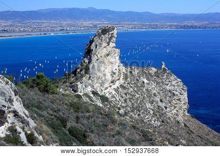 Seascape with a famous rock Sella del Diavolo - the Devil's Saddle the beach il Poetto and the city Cagliari in Sardinia Italy.