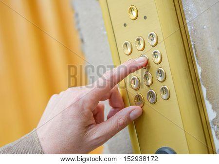 Close-up hand of person using building intercom
