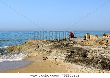 people sitting on the rocks on the shore of the Mediterranean Sea