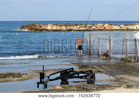 fishermen with fishing poles on the Mediterranean coast in northern Israel