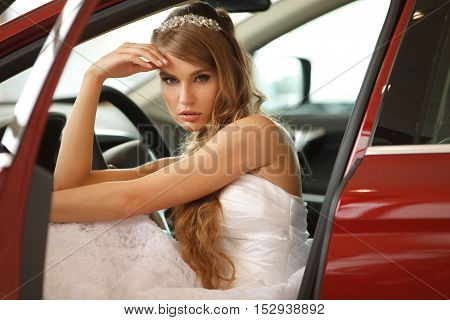 Young sensual bride sits in the red car.Selective focus. Professional hair and make -up