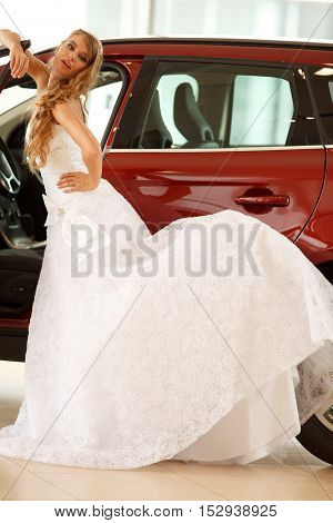 Young  beautiful bride standing near red car