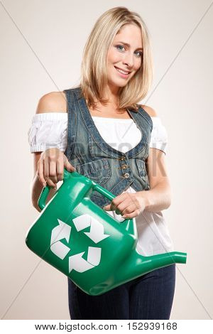 Going green! Woman holding a green watering pot with recycling sign