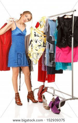 Woman is trying on dresses ;near her clothes rack with lots of dresses