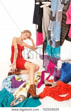 Sad young woman sits near her clothes rack with lots of dressesand some clothes is on the floor.