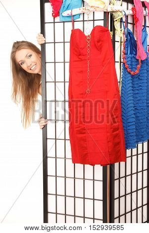 Young beautiful woman looks out of the folding screen lots of clothes and underwear hang on it