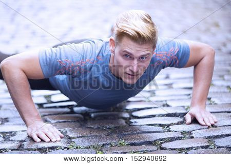 young handsome man doing pushups outdoors on cobblestone