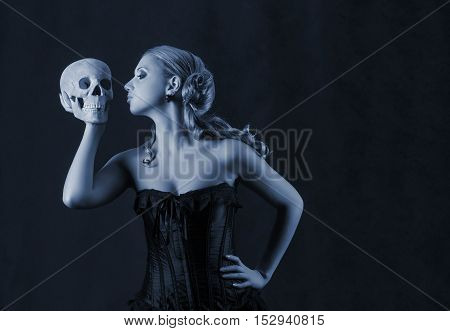 Beautiful woman with a skull low key portrait