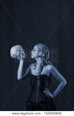 Beautiful woman with a skull low key portrait