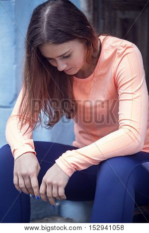 young sporty brunette woman sitting on stairs and looking to the ground