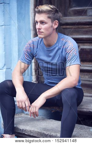 handsome young blond sportsman sitting on stairs
