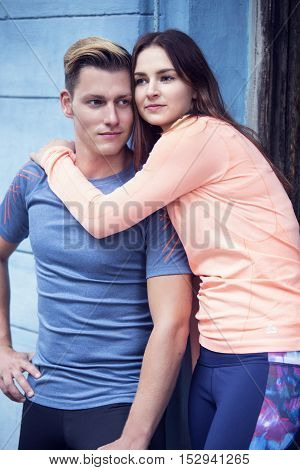 portrait of sporty young couple standing on wall