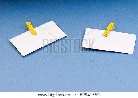 a blank card with space for notes on the wooden clothespin colored paper on blue background