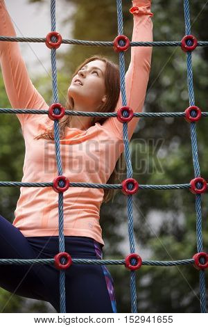 young beautiful sporty woman climbing up a net outdoors