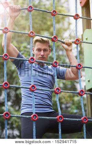 young handsome sportsman climbing up a net outdoors