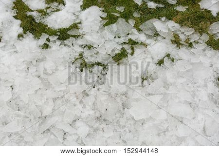Ice on a grass. Snow on a grass. Spring in mountains.