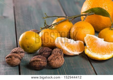 Tangerines with branch leafs orange slices and wallnuts on green wooden table. Selective focus.