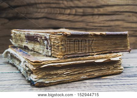 Old tattered book on a wooden table