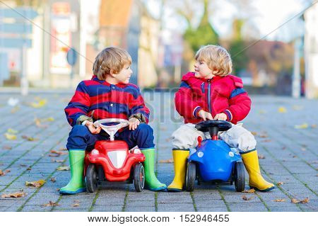 Two little kids boys in colorful clothes and rain boots driving toy cars. Twins making competition, outdoors. Active leisure for children on autumn day