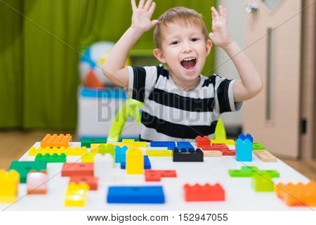 Boy in the children's room plays in the constructor on the table