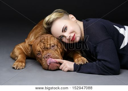 Beautiful young woman in casual clothes hugging big brown dogue de bordeux dog over black background.