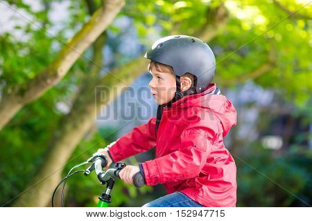 Active little preschool kid boy in helmet biking on bicycle in the autumn park. Happy child in colorful clothes with yellow fall foliage on background. Safety and protection for children.