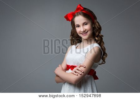 Beautiful teenage girl with long curly hair and red ribbon bow on head wearing white dress. Happy expression. Studio portrait on grey background. Copy space.
