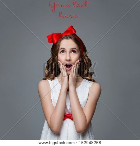 Beautiful teenage girl with long curly hair and red ribbon bow on head wearing white dress. Surprised expression. Studio portrait on grey background. Copy space.