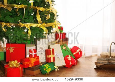 Colorful boxes with presents under Christmas tree