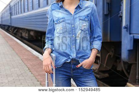 Young woman standing on railway platform near train, closeup