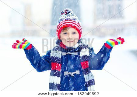 Funny little kid boy in colorful clothes playing outdoors during snowfall. Active leisure with children in winter on cold snowy days. Happy child having fun with snow