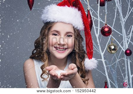 Beauiful girl in red santa cap showing snow on palms of hands. Happy expression. Studio shot on christmas ornament background with falling snow. Copy space.