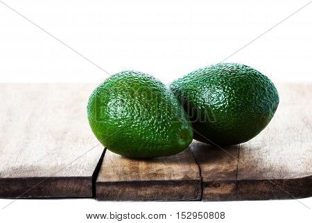 Food background with fresh organic avocado on a cutting board isolated over white