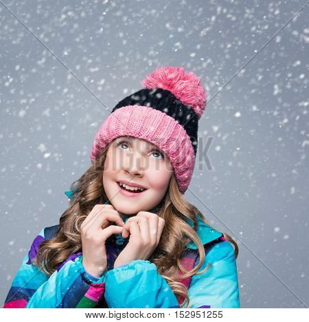 Beautiful happy teen girl with long curly hair in pink wool hat and bright warm coat looking up. Studio shot over grey background with falling snow. Copy space. Square composition.