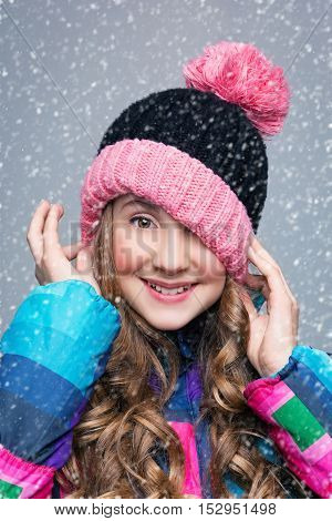 Beautiful happy teen girl with long curly hair in pink wool hat and bright warm coat. Studio shot over grey background with falling snow. Copy space.