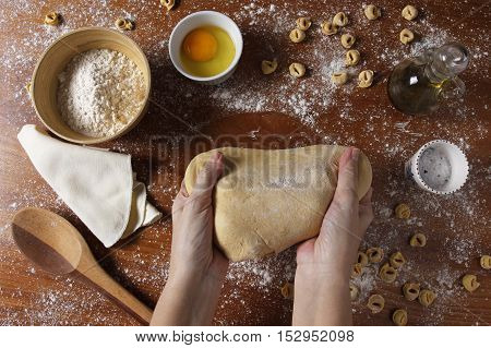 Female hands kneading dough on wooden table with ingredients. Top view. Rustic style