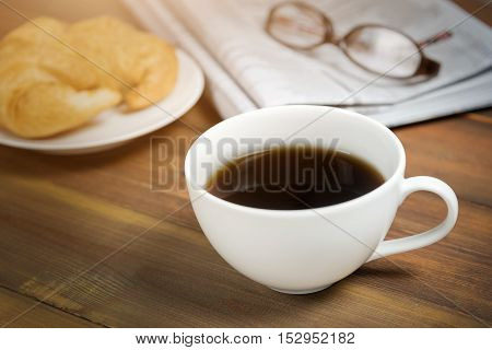 Coffee cup with newspaper and glasses in background on wooden table.