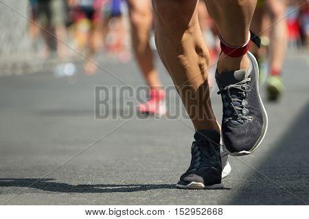 Marathon runners race, detail running shoes on asphalt