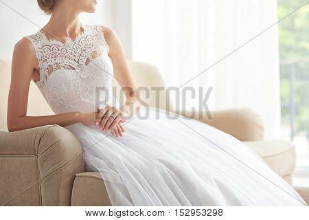 Bride in beautiful wedding gown sitting on sofa