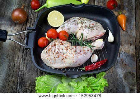 Raw chicken drumstick with spices (seasoning) in pan - chicken raw meat ready to prepare meal