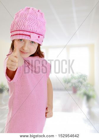 Cheerful little girl in a pink knitted dress and hat, shows hand gesture all right, thumb to the top.In the room with the big bright window in the wall.
