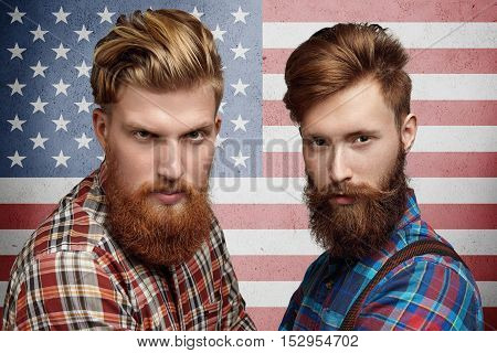Emotions patriotism citizenship and people. Two serious and confident American patriots with stylish haircuts and beards posing against US flag. Portrait of Caucasian friends in hipster shirts