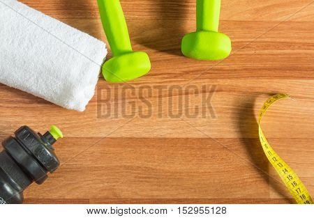 Fitness concept with dumbbells, water bottle, measuring tape, towel on wooden background.