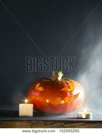 Halloween pumpkin with candles and smoke on a dark background