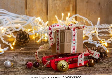 Handmade gift box on sledge with christmas lights on wooden background