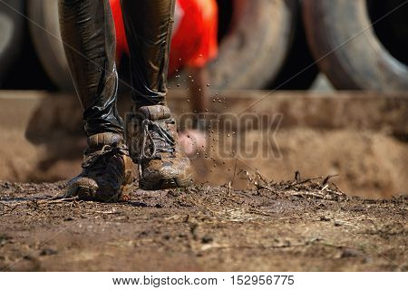 Mud race runners, detail of the legs in the background obstruction tires