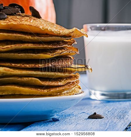 Stack of prepared pumpkin pancakes with chocolate drops and glass of milk on the big orange pumpkin background