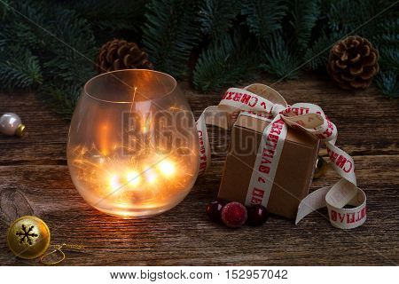 Christmas magic glowing light with handmade gift box and evergreen twig on wooden background