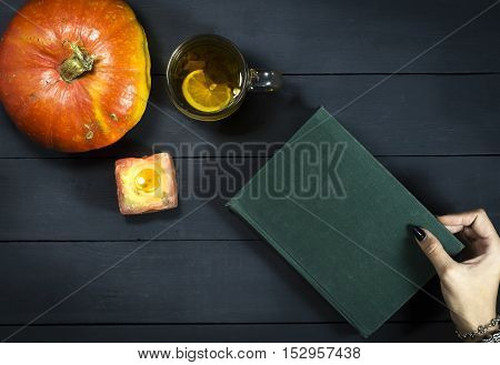 The book is in a female hand over the table with a cup of tea and a pumpkin